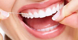 woman flossing dental implants gum disease